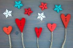 Knöpfen Sie Liebesbäume unter Schneeflocke auf grauem hölzernem Hintergrund Stockbild