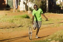 Knabe, der mit Rad-Felge spielt Lizenzfreies Stockfoto