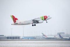 KNACKA LÄTT PÅ den Air Portugal flygbussen A319-100 CS-TTF i den Munich flygplatsen, Tyskland, vintertid med snö royaltyfri fotografi