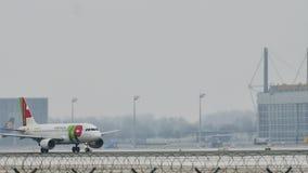 KNACKA LÄTT PÅ den Air Portugal flygbussen A319-100 CS-TTF i den Munich flygplatsen, Tyskland, vintertid med snö lager videofilmer