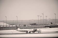 KNACKA LÄTT PÅ den Air Portugal nivån på landningsbana i den Munich flygplatsen, Tyskland, vintertid med snö royaltyfri foto