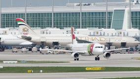 KNACKA LÄTT PÅ den Air Portugal nivån som åker taxi på landningsbana i den Munich flygplatsen, Tyskland lager videofilmer