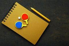 Knacka pongracket klumpa ihop sig blyertspennaanteckningsboken asfalterar inget royaltyfri fotografi