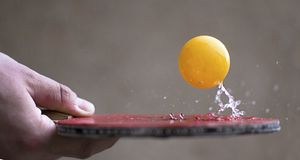 Knacka pongracket som slår en boll Rörelsehandlingbegrepp av bordtennissporten arkivfoto