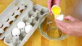 Knacken eines Eies in eine Schüssel stock video footage