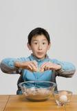 Knackendes Ei des jungen Jungen in Schüssel lizenzfreies stockfoto