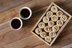 Knafeh гнезда Bulbul - ближневосточное сладостное bolbol el aysh блюда и арабский кофе Qahwah с деревянной предпосылкой стоковые изображения