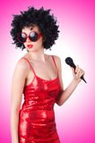 Knal ster met mic in rode kleding stock foto