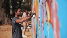 Knap begaafd paar van jongen en meisje die een kleurrijke graffiti met aërosolnevel maken op stedelijke straatmuur stock footage