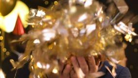 Knap blij mannetje die op confettien blazen en pret hebben bij verjaardagspartij stock videobeelden