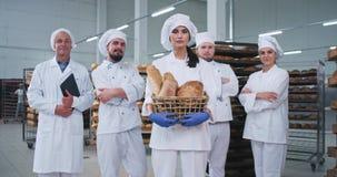 Knap groot hoofdteam van een bakkerijfabriek die een mand met vers gebakken brood houden die recht aan de camera kijken stock footage