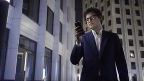 Knap jong zakenmanweb die in een nachtstad surfen stock videobeelden