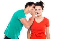 Knap jongen het spreken geheim aan jong meisje stock foto's