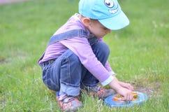 Knap jongensspel met het vliegen op het gras stock foto
