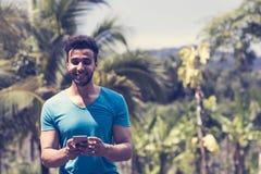 Knap Latijns Mensenoverseinen met Cel Slimme Telefoon over Tropisch Forest Background, Portret van Jong Guy Chatting royalty-vrije stock afbeeldingen
