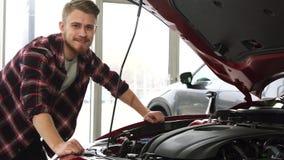 Knap mannetje die cutomer motor van een auto onderzoeken bij de het handel drijventoonzaal stock fotografie