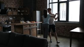 Knap mensen uitnodigend meisje om in de keuken te dansen stock videobeelden