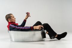Knap modelmannetje met kort kapsel in vrijetijdskledingszitting in het metaalbad in studio royalty-vrije stock foto