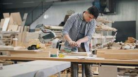 Knap timmerman het oppoetsen stuk van hout met elektrische machine stock video