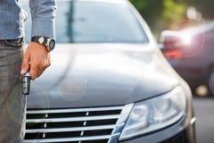 Knapp för bil för trycka på för hand för man` s en avlägsen som öppnar eller som stänger bildörrlåset Lycklig ägare av bilen Arkivbild