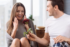 Knappe aardige mens die een bloem geven aan zijn meisje royalty-vrije stock afbeelding