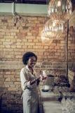 Knappe Afrikaans-Amerikaanse bararbeider die met glazen belast die bij bar oppoetsen royalty-vrije stock afbeelding