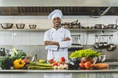 knappe Afrikaanse Amerikaanse chef-kok die zich bij restaurantkeuken bevinden met gekruiste wapens en het kijken stock afbeeldingen