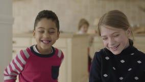 Knappe Afrikaanse Amerikaanse jongen en vrij blond Kaukasisch meisje die pret in de keuken hebben Het jongen het fluisteren gehei stock videobeelden