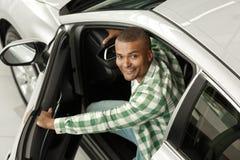 Knappe Afrikaanse mens die nieuwe auto kiezen bij het handel drijven stock foto's