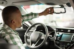 Knappe Afrikaanse mens die nieuwe auto kiezen bij het handel drijven royalty-vrije stock afbeeldingen