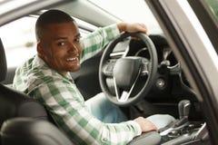 Knappe Afrikaanse mens die nieuwe auto kiezen bij het handel drijven royalty-vrije stock foto's