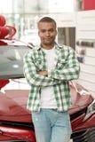 Knappe Afrikaanse mens die nieuwe auto kiezen bij het handel drijven stock foto