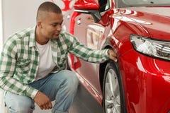 Knappe Afrikaanse mens die nieuwe auto kiezen bij het handel drijven royalty-vrije stock fotografie