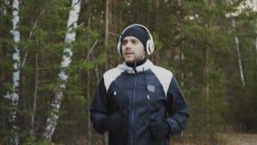 Knappe agentmens in hoofdtelefoons die terwijl het luisteren muziek in de winterpark in de ochtend aanstoten stock footage
