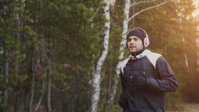 Knappe agentmens in hoofdtelefoons die terwijl het luisteren muziek in de winterpark in de ochtend aanstoten stock afbeelding