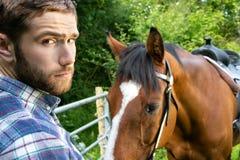 Knappe Amerikaanse cowboy, ruiter met gecontroleerde, geruite overhemd en jeanshuisdieren en liefdes zijn paard stock foto