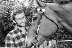 Knappe Amerikaanse cowboy, ruiter met gecontroleerde, geruite overhemd en jeanshuisdieren en liefdes zijn paard royalty-vrije stock foto's