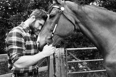Knappe Amerikaanse cowboy, ruiter met gecontroleerde, geruite overhemd en jeanshuisdieren en liefdes zijn paard stock afbeelding