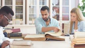 Knappe Arabische jonge gebaarde mens die door multiraciale studenten wordt omringd die in handen groot oud boek in bibliotheek ho stock footage