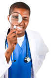 Knappe arts die door een vergrootglas kijkt Stock Fotografie