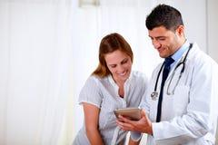 Knappe arts en een vrouw die aan tabletPC kijkt Royalty-vrije Stock Foto