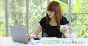 Knappe Aziatische boekhouding in het bureau stock videobeelden