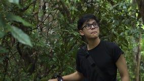 Knappe Aziatische kerel die door het bos overgaan