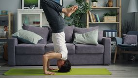 Knappe Aziatische kerel die headstand tijdens yogapraktijk thuis doet alleen stock video