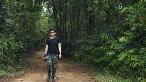Knappe Aziatische kerel die rond het bos benieuwd zijn om te verfrissen stock footage