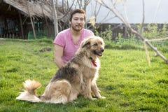 Knappe Aziatische mens en zijn pluizige hond op een zonnige dag in een tuin Royalty-vrije Stock Foto's