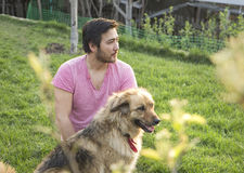 Knappe Aziatische mens en zijn pluizige hond op een zonnige dag in een tuin Royalty-vrije Stock Foto