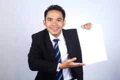 Knappe Aziatische zakenman die een leeg document met het richten van gebaar houden Stock Foto's