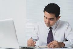 Knappe Aziatische zakenman die ernstig in het bureau werken Stock Fotografie
