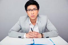 Knappe Aziatische zakenman die in glazen bij de lijst met pen a zitten Stock Foto's